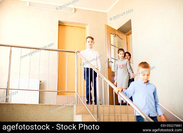 Schoolchildren in the school hallway go downstairs during the break