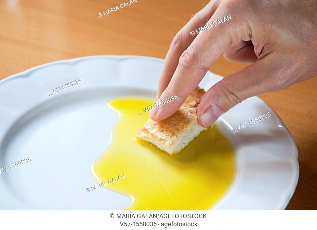 Man's hand dipping bread in olive oil. Close view