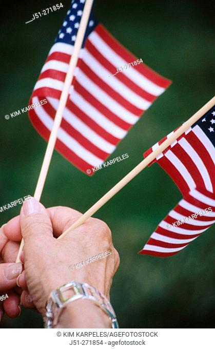 Woman holding american flags on the fourth of July parade. Illinois