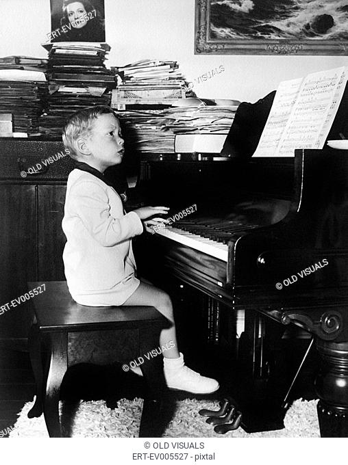 Profile of a boy sitting on a stool and playing a piano All persons depicted are not longer living and no estate exists Supplier warranties that there will be...