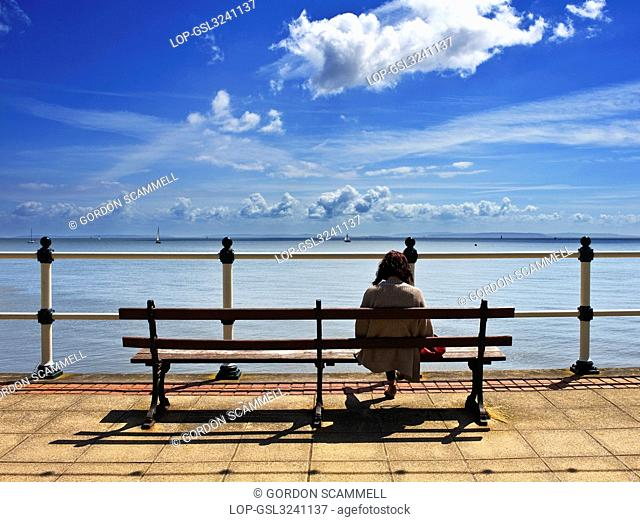 Wales, The Vale of Glamorgan, Penarth. A woman sitting on a bench looking out to sea on Penarth Esplanade
