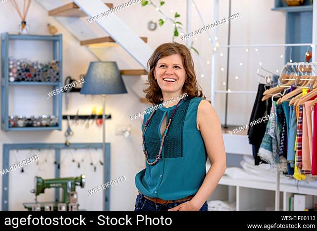 Happy fashion professional looking up while standing at illuminated design studio