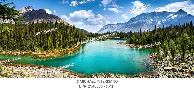 Colourful alpine lake with mountains, blue sky and clouds in the background; British Columbia, Canada