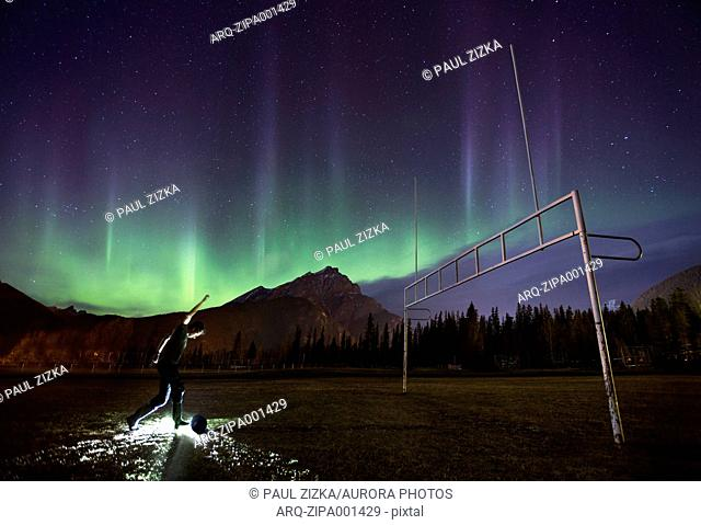 Person Playing Soccer Under Aurora Borealis