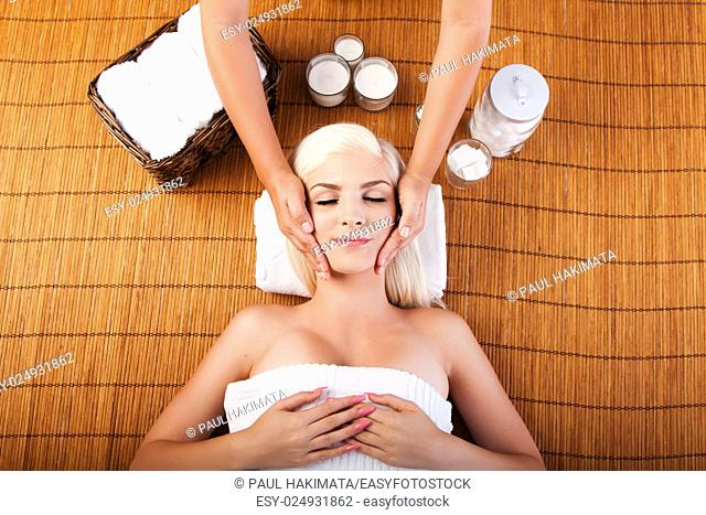 Beautiful young woman relaxing at spa getting therapeutic pampering facial massage, laying on bamboo