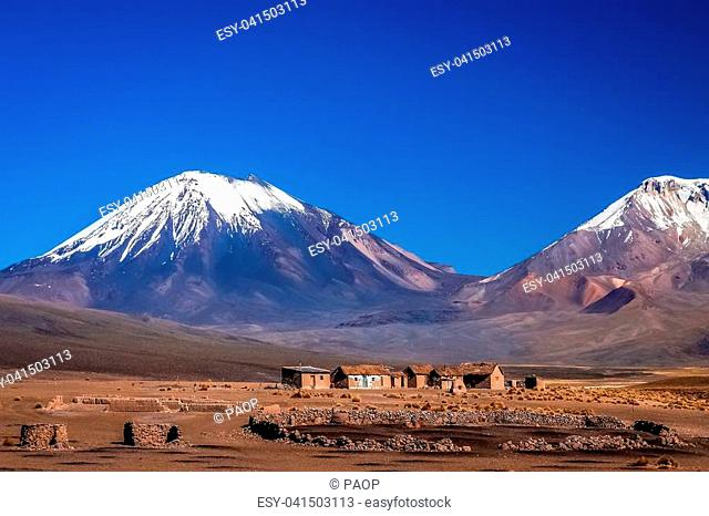 Abandoned homes and houses at the foot of two enormous volcanos, Nevado Sajama and Parinacota in the National Park, Bolivia