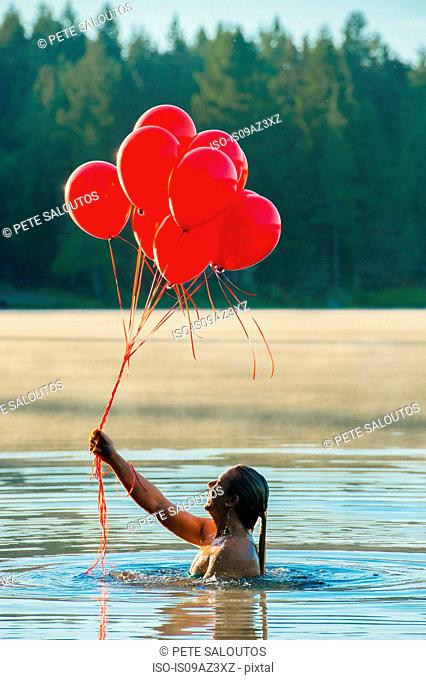 Woman in water holding bunch of red balloons