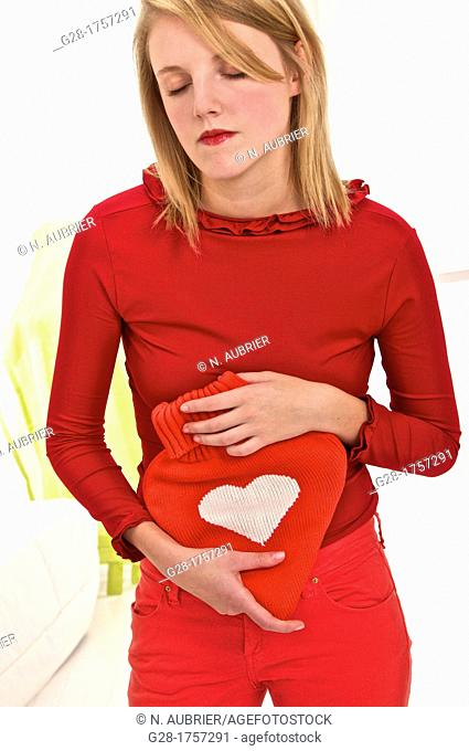 Young blond woman holding a red heart shaped hot water bottle