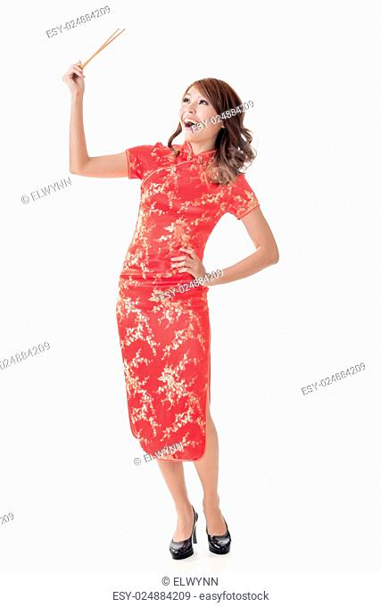 Smiling Chinese woman dress traditional cheongsam standing and holding chopsticks at New Year, full length portrait isolated