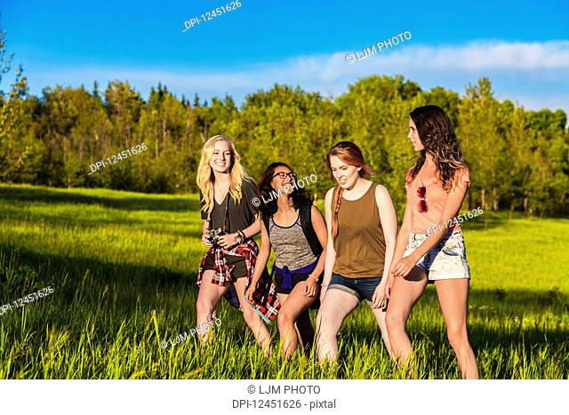 A group of four girlfriends hike together through a field in a park; Edmonton, Alberta, Canada