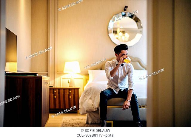 Man sitting on bed in hotel room, having drink