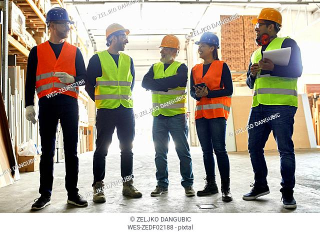 Smiling workers standing in factory workshop talking