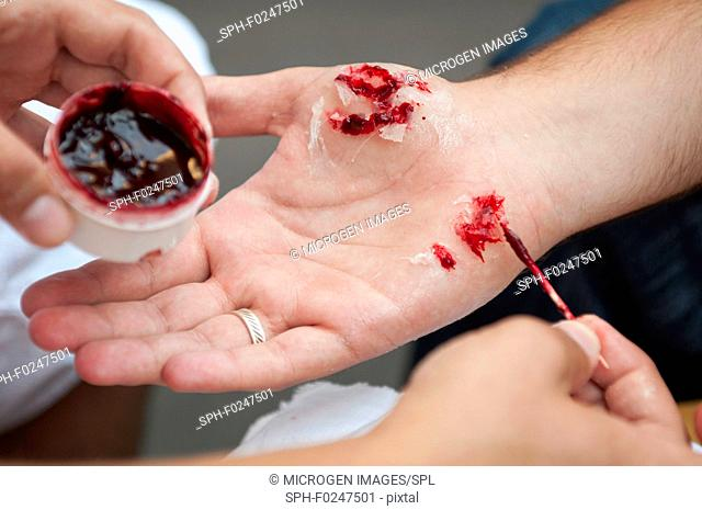 Special effects make up artist creating realistic hand injuries