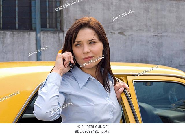portrait of young businesswoman standing at open door of yellow taxi listening to mobile phone