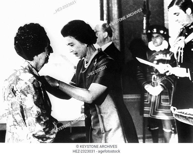 Queen Elizabeth II presents the BEM to Miss Margaret Aiken, Northern Ireland, 1977. The service took place at Hilleborough Castle