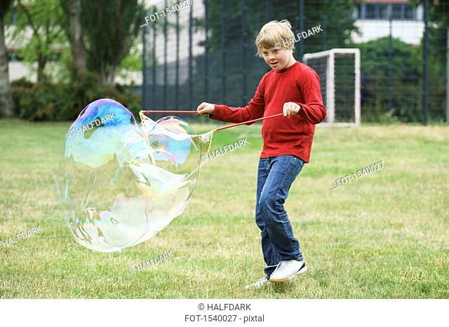 Disabled boy playing with soap bubbles in park