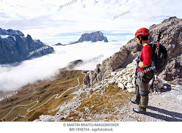 Climber on the way up to Gran Cir mountain above the Gardena Pass, Dolomites, Val Gardena valley and Langkofel mountain at the back, province of Bolzano-Bozen