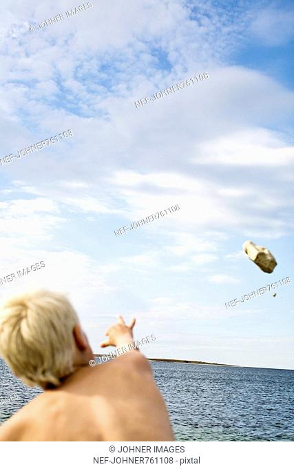 Boy throwing a stone by the sea, Sweden