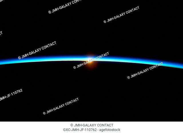 The thin line of Earth's atmosphere and the setting sun are featured in this image photographed by a crew member on the International Space Station while space...