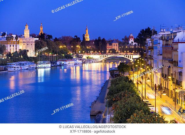 Guadalquivir river Triana quarter at right and Gold tower  In the background towers of España square  Seville, Andalusia, Spain