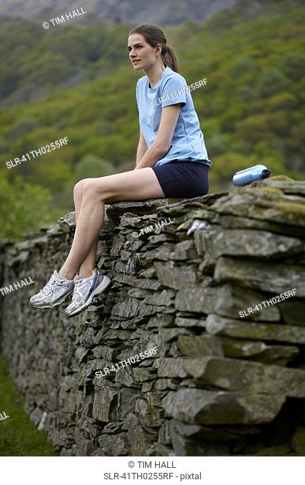 Runner sitting on rock wall