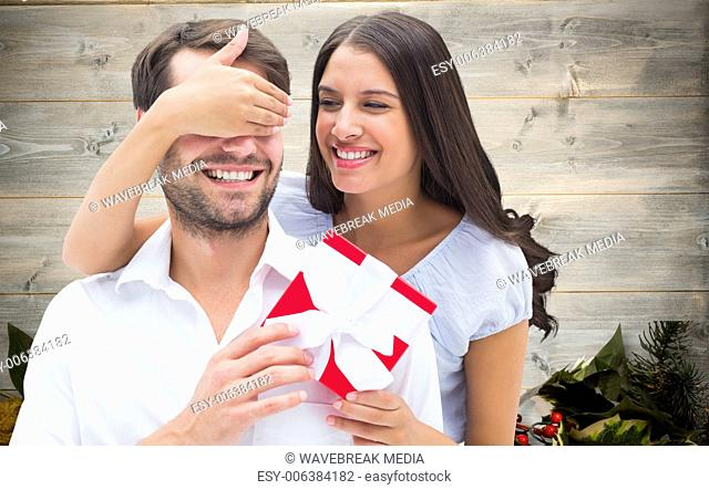 Composite image of woman surprising boyfriend with gift