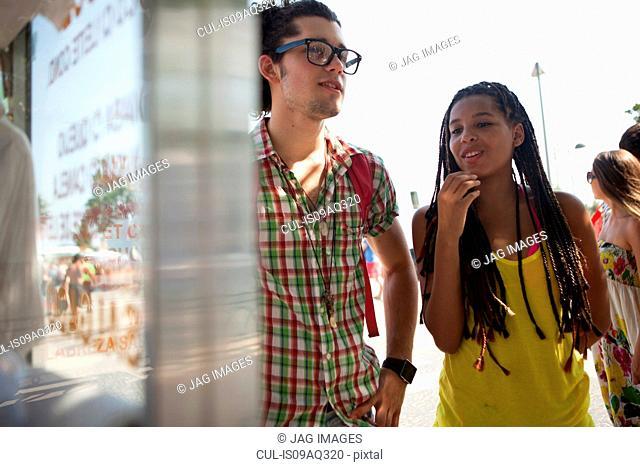 Young couple reading food stall menu, Copacabana, Rio De Janeiro, Brazil