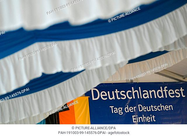 "03 October 2019, Thuringia, Mödlareuth/Töpen: In the marquee of the CDU/CSU a banner with the inscription """"Deutschlandfest - Tag der Deutschen Einheit"""" can be..."