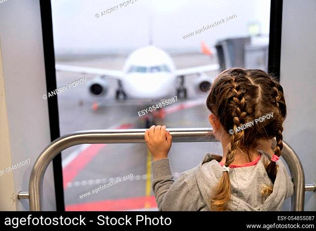 Girl Looking At Airplane Before Boarding For Family Vacation