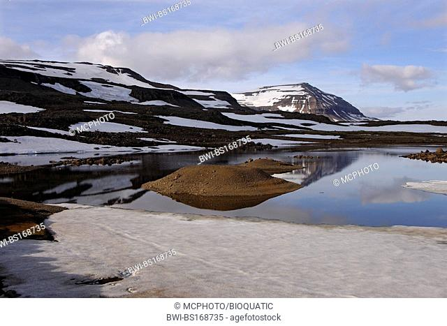 Meltwater pool and the mountain Bjolfur in the Fjardarheidi range near Seydisfjordur, Iceland