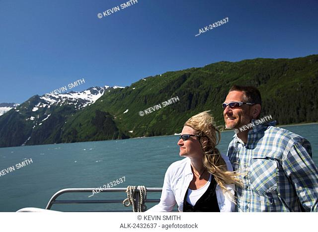 Couple enjoy sun in their faces while on a water taxi in Shoup Bay, Shoup Bay State Marine Park, Prince William Sound, Southcentral Alaska