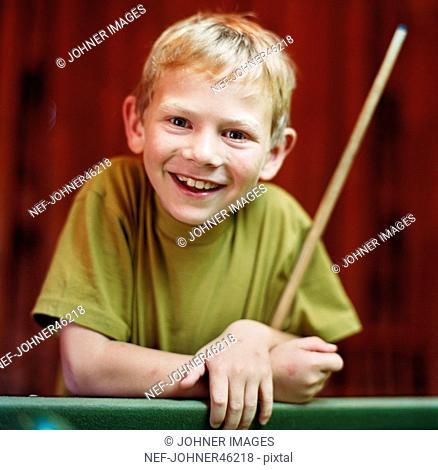 Portrait of boy holding pool cue