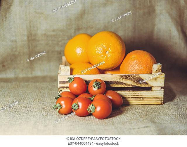 Oranges in crate and cherry tomatoes together on rustic sackcloth background