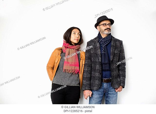 Persian man and Tibetan woman holding hands and leaning against a wall, man looking away while woman is looking at man; Toronto, Ontario, Canada