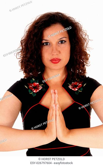A gorgeous woman with curly brunette hair folding her hands and.praying, isolated for white background.