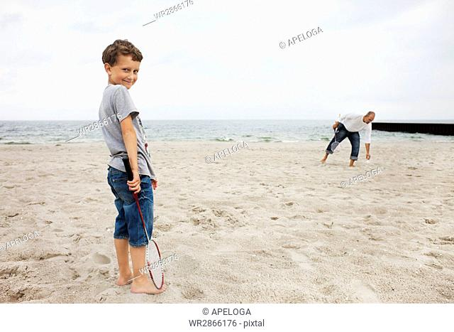 Portrait of boy standing with father at beach