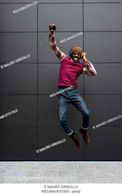 Man jumping in the air while listening music with headphones and cell phone