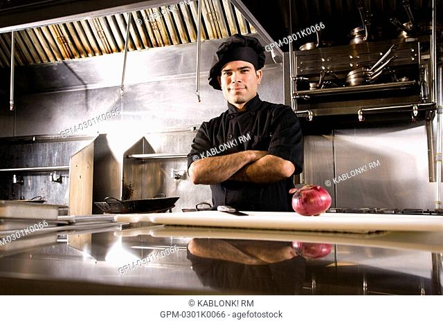 Portrait of Cuban chef standing in restaurant kitchen with cutting board and red onion