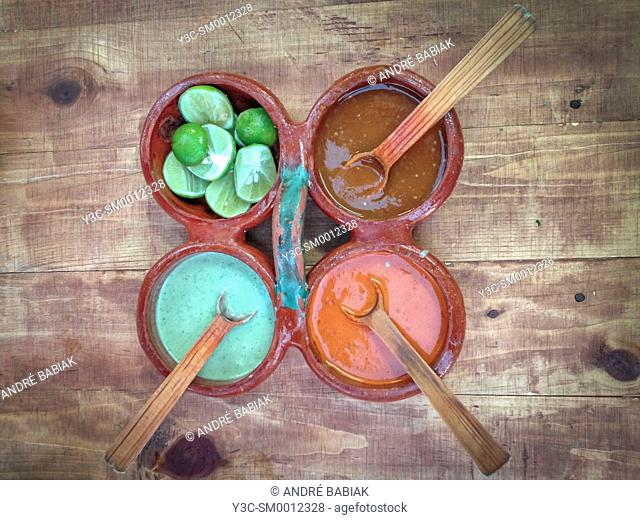 Mexican food - Rustic ceramic tray with 4 separate bowls for condiments. Used for different salsas and lime