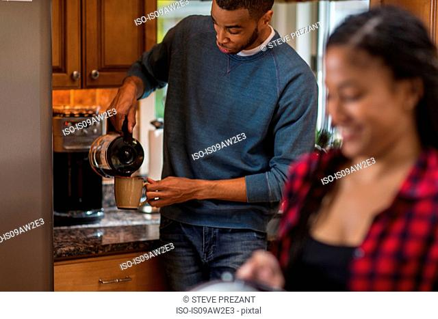 Mid adult couple pouring coffee in kitchen