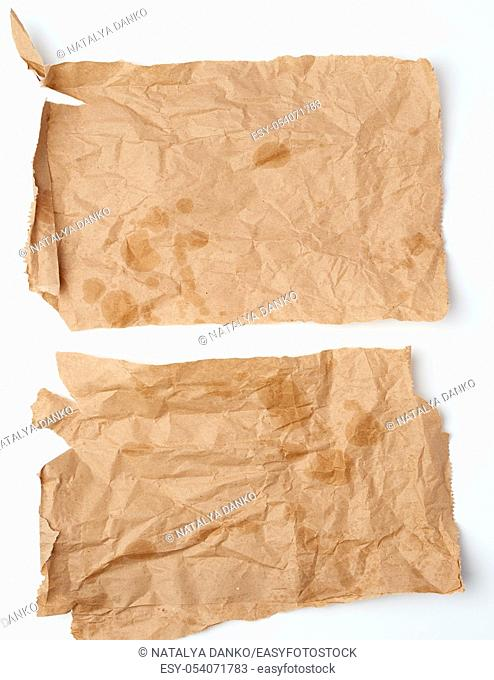 torn crumpled pieces of brown paper with grease stains on a white background, top view
