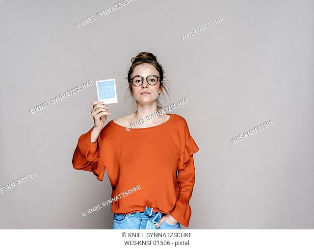 Portrait of young woman holding instant photo