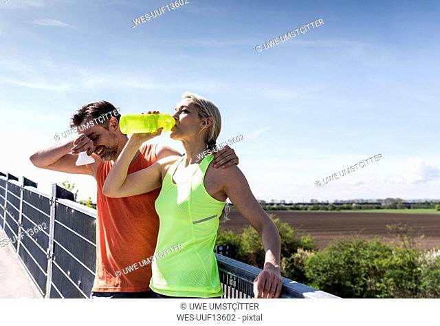 Fit couple jogging in the city, having fun, taking a break
