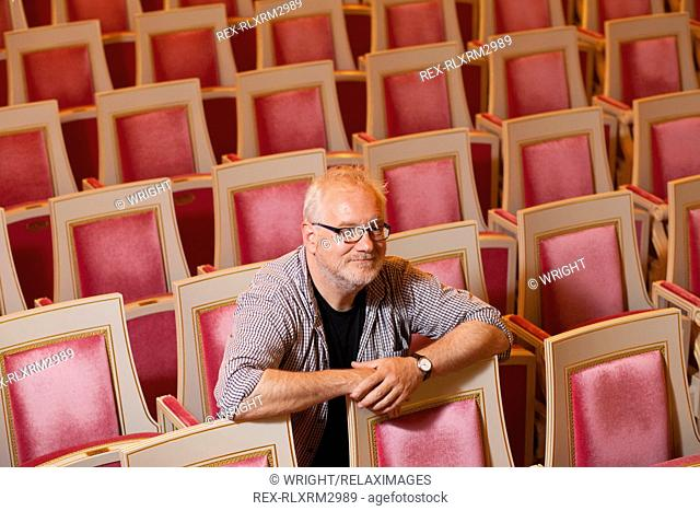 Confident mature stage designer sitting alone in National Theatre Munich