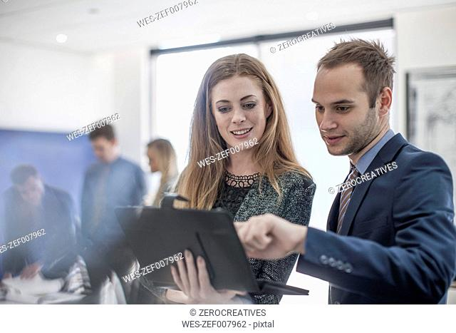 Businessman and woman in office looking at digital tablet