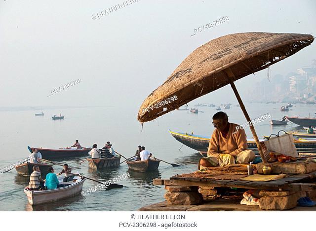 India, Bihar, Priest Sits Under An Umbrella On Varanasi Ghats; Bodhgaya