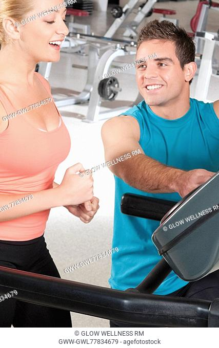 Man assisting a woman on a treadmill