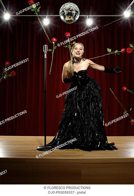 Woman on stage with microphone having roses thrown at her