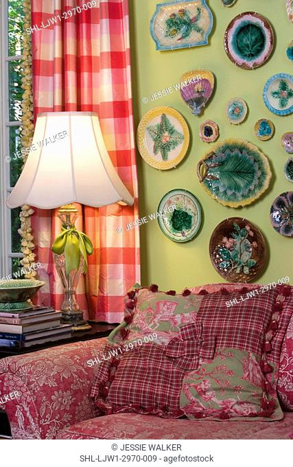 LIVING ROOMS: Bright green walls with bright raspberry accent colors, collection displays of majolica plates on wall, toile sofa and pillow