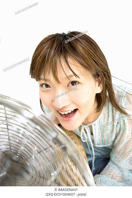 A woman in front of fan